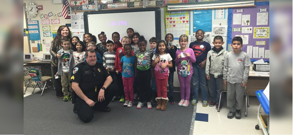 Police officer standing in a classroom with school children and teacher
