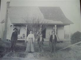 Three people standing in front of a small house in a black and white photograph