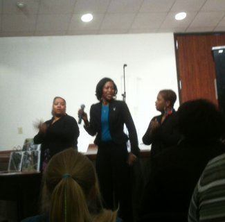 Woman holding a microphone standing with several other people giving a presentation